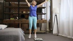 Симпатичная женщина пригонки празднуя потерю веса внутри помещения сток-видео