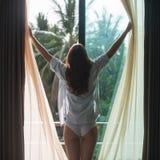Симпатичная женщина проснулась и стоящ перед окном стоковая фотография