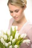 Симпатичная женщина смотря вниз с белых цветков тюльпана Стоковое Изображение RF