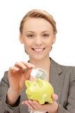 Симпатичная женщина с копилкой и деньгами Стоковое фото RF