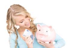 Симпатичная женщина с копилкой и деньгами Стоковое Изображение