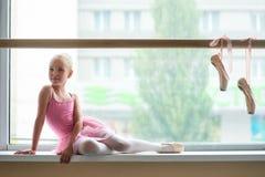 Симпатичная маленькая балерина представляя на окн-силле Стоковые Фото