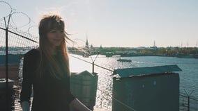 Симпатичная маленькая девочка в черном платье на крыше с сценарным взглядом реки города сток-видео
