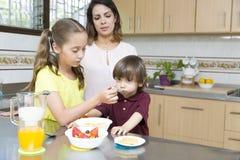 Симпатичная мать и ее дети имея завтрак Стоковое Изображение