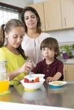 Симпатичная мать и ее дети имея завтрак Стоковое Изображение RF