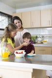 Симпатичная мать и ее дети имея завтрак Стоковые Изображения RF