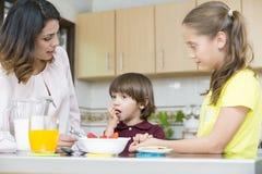 Симпатичная мать и ее дети имея завтрак Стоковые Фото
