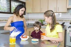Симпатичная мать и ее дети имея завтрак Стоковое фото RF