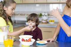 Симпатичная мать и ее дети имея завтрак Стоковые Изображения