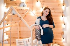 Симпатичная молодая беременная женщина стоя на предпосылке деревянной стены Стоковая Фотография
