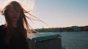 Симпатичная молодая женщина в черном платье на крыше с сценарным взглядом реки города сток-видео