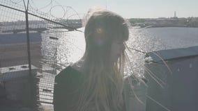 Симпатичная молодая женщина в черном платье на крыше с сценарным взглядом реки городка видеоматериал