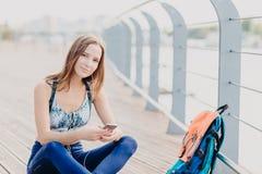 Симпатичная молодая женщина с телом пригонки, остатками после cardio тренировки, одела в sportswear, держит современный сотовый т стоковое фото
