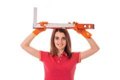 Симпатичная молодая дама брюнет делает реновацию в перчатках с уровнями здания в ее изолированных руках на белой предпосылке Стоковое Изображение RF