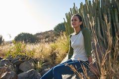 Симпатичная молодая дама сидя на утесе Стоковое Изображение