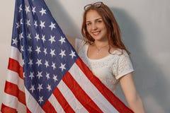 Симпатичная молодая женщина с объединенным флагом ` s положения в фронте на ее усмехаться тела Стоковое Изображение RF