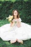 Симпатичная невеста сидя на земле держа букет усмехаясь на камере Стоковые Изображения RF