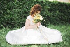 Симпатичная невеста сидя на земле держа букет усмехаясь на камере Стоковое фото RF