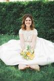 Симпатичная невеста сидя на земле держа букет усмехаясь на камере Стоковая Фотография RF