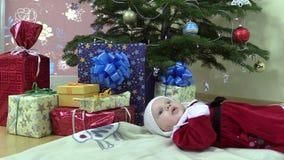 Симпатичная ложь ребёнка около коробок рождественской елки и подарка присутствующих сток-видео