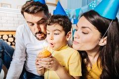Симпатичная семья делая желание пока дующ вне свеча Стоковые Фото