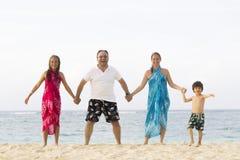 Симпатичная семья наслаждаясь на пляже Стоковые Изображения