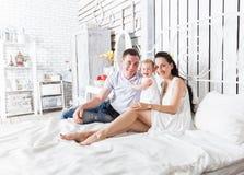 Симпатичная семья сидя совместно на кровати Стоковое Фото