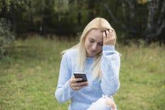Симпатичная усмехаясь девушка читает sms на мобильном телефоне, Стоковые Изображения