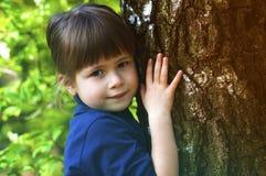 Симпатичная усмехаясь маленькая девочка стоя около большого дерева на зеленой траве Стоковые Изображения RF