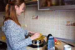 Симпатичная усмехаясь молодая женщина делая макаронные изделия в кухне Стоковое фото RF
