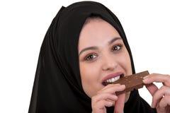 Симпатичная усмехаясь мусульманская женщина с hijab есть шоколад изолированный на белой предпосылке Стоковое Изображение