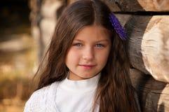 Симпатичная long-haired девушка против деревянной загородки стоковая фотография rf