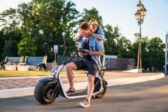 Симпатичное молодое датировка пар с электрическим велосипедом стоковая фотография
