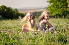 Симпатичные белокурые девушки сидя в луге Стоковые Изображения
