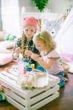 Симпатичные девушки сестры красят яичка и имеют потеху подготавливая для пасхи Стоковое Изображение RF