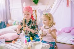 Симпатичные девушки сестры красят яичка и имеют потеху подготавливая для пасхи Стоковые Изображения RF