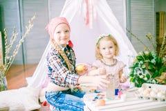 Симпатичные девушки сестры красят яичка и имеют потеху подготавливая для пасхи Стоковые Изображения