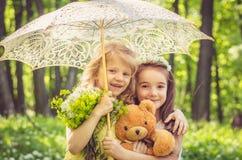 Симпатичные девушки держа плюшевый медвежонка и зонтик Стоковая Фотография