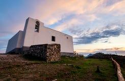 Симпатичные золотые часы освещают на церков San Costanzo под красочными облаками стоковые изображения rf