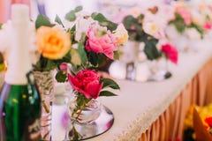 Симпатичные мини-вазы с красочными розами на комплекте таблицы wed Стоковая Фотография