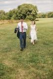 Симпатичные пары идя на зеленый луг Стоковая Фотография RF