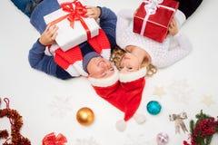 Симпатичные пары рождества лежа с настоящими моментами Стоковые Изображения