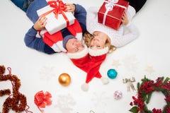 Симпатичные пары рождества лежа с настоящими моментами Стоковые Фотографии RF