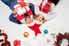 Симпатичные пары рождества лежа с настоящими моментами Стоковые Фото
