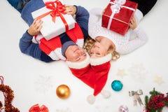 Симпатичные пары рождества лежа с настоящими моментами Стоковое Фото