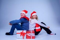 Симпатичные пары рождества сидя с настоящими моментами Стоковое Изображение RF