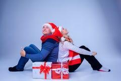 Симпатичные пары рождества сидя с настоящими моментами Стоковые Изображения RF