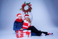 Симпатичные пары рождества сидя с настоящими моментами Стоковое Фото