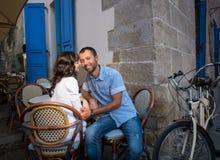 Симпатичные пары сидя в кафе тротуара около их тандемного велосипеда стоковые фотографии rf