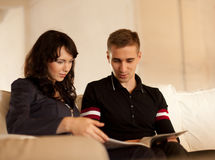 Симпатичные пары читая книгу совместно Стоковое Фото